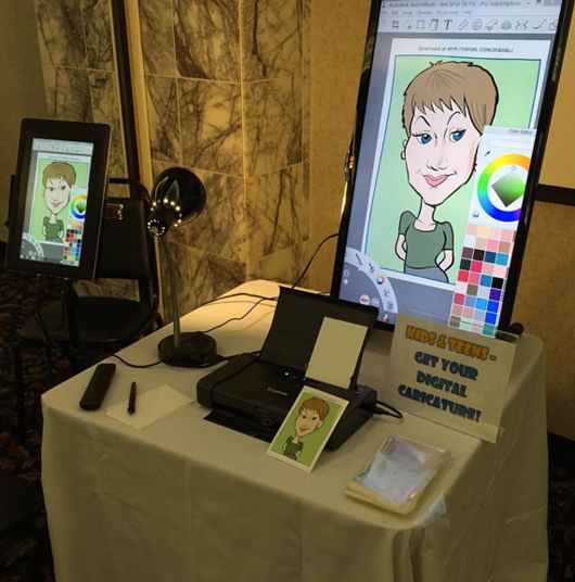 The digital caricature setup, including the tablet, printer and display screen.